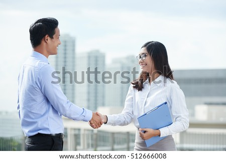 Smiling Vietnamese business executive shaking hands outdoors