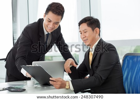 Smiling Vietnamese businessman and his young colleagues discussing a document - stock photo