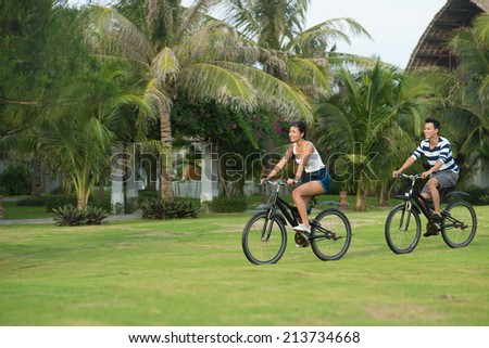 Smiling Vietnamese couple riding on bikes in the park: health lifestyle concept - stock photo
