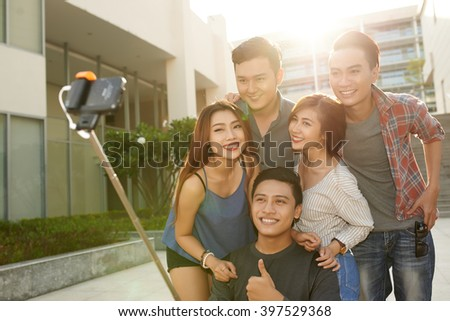 Smiling Vietnamese guys and girls taking selfie together