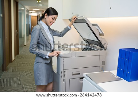 Smiling Vietnamese secretary scanning a document - stock photo