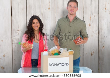 Smiling volunteers taking out food from donations box against wooden background - stock photo