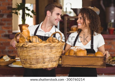 Smiling waiter and waitress holding basket full of bread rolls at coffee shop - stock photo
