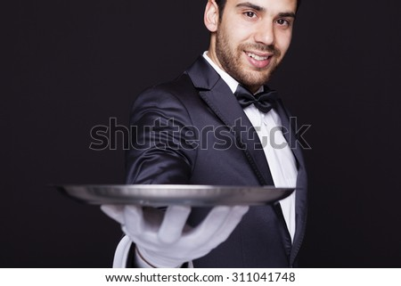 Smiling waiter holding an empty silver tray against dark background - stock photo