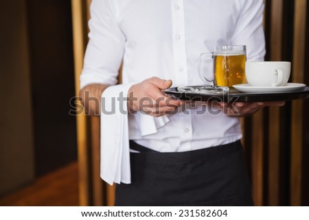 Smiling waiter holding tray with coffee cup and pint of beer in a bar - stock photo
