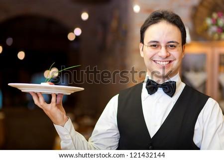 Smiling waiter in an elegant restaurant - stock photo
