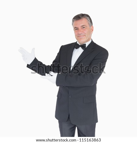 Smiling waiter in suit showing us something