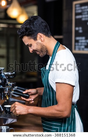 Smiling waiter making cup of coffee at the coffee shop - stock photo