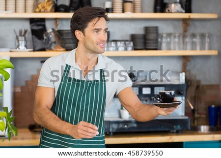 Smiling waiter offering a cup of coffee at cafe