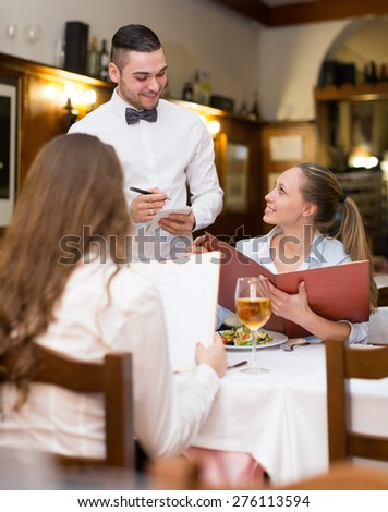 Smiling waiter serving bar guests with the beverages   - stock photo
