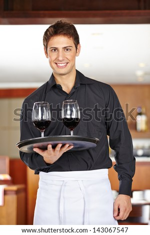 Smiling waiter serving red wine in a restaurant