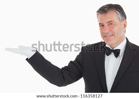 Smiling waiter showing us something in his opened hand