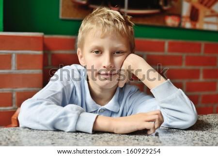 smiling waiting boy looking at the camera  - stock photo