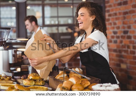 Smiling waitress giving paper bag to customer at coffee shop - stock photo