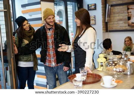 Smiling waitress greeting entering young couple in cafeteria.