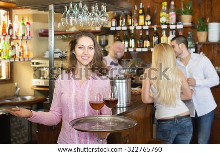 Smiling waitress holding tray with glasses of wine in bar