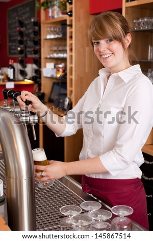 Smiling waitress pouring draft beer from a metal spigot on the keg behind the bar counter