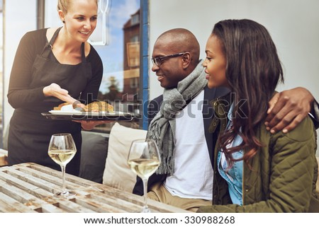 Smiling waitress serving a loving African American couple their food as they sit arm in arm at a restaurant table - stock photo