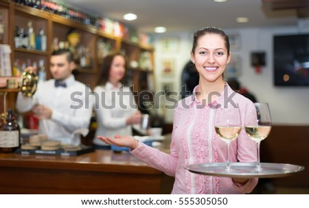 Smiling waitress with beverages and bar crew at background