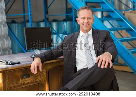 Smiling warehouse manage sitting with his legs crossed in a large warehouse - stock photo