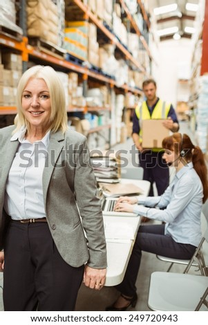 Smiling warehouse manager leaning on desk in a large warehouse