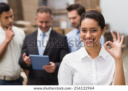 Smiling warehouse manager making okay gesture in a large warehouse - stock photo
