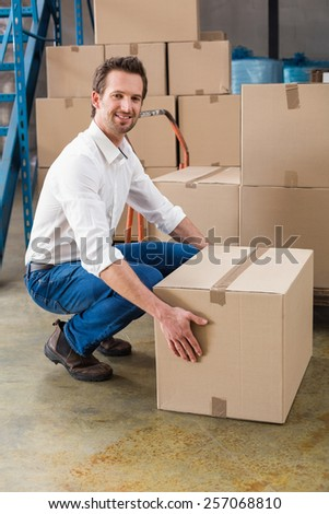 Smiling warehouse manager with box in warehouse