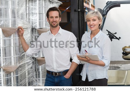 Smiling warehouse managers checking inventory in a large warehouse - stock photo