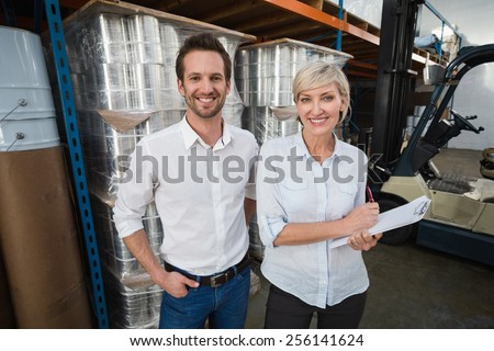 Smiling warehouse managers looking at camera in a large warehouse - stock photo