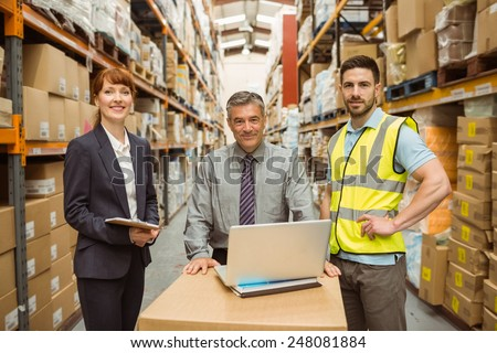 Smiling warehouse team working together on laptop in a large warehouse