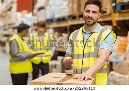 Smiling warehouse workers preparing a shipment in a large warehouse - stock photo
