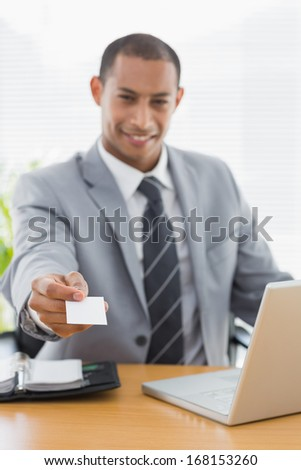 Smiling well dressed young man handing over his business card in front of laptop at office desk - stock photo