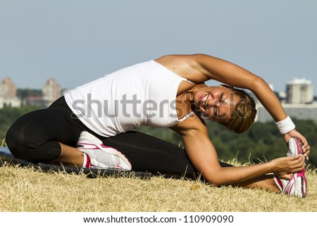 Smiling while doing heavy exercises. Shot taken outside on an early morning sun. - stock photo