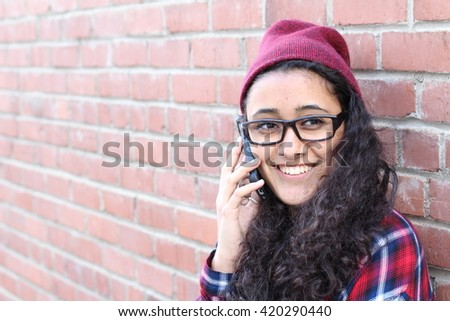Smiling Winter Hipster Girl in Plaid Shirt and Beanie Hat with Mobile Phone Isolated on Brick Wall. Teenage Communication Concept. - stock photo