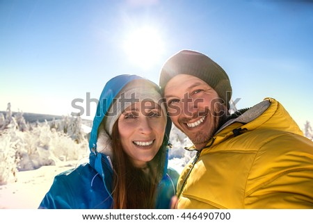 smiling wintersport selfie in the mountains - stock photo