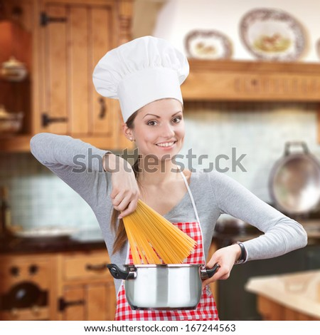 Smiling woman adding pasta to the pot