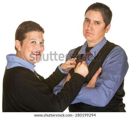 Smiling woman adjusting necktie of serious girlfriend - stock photo