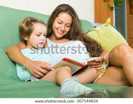 Smiling woman and child reading book. Focus on mother - stock photo