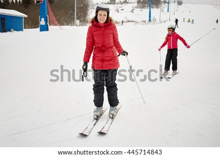 Smiling woman and girl in red jackets on snowy slope at ski resort.