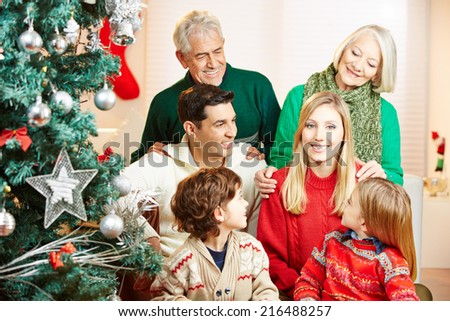Smiling woman and her family celebrating christmas at home with tree