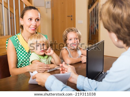 Smiling woman and two little daughters sitting in front of social worker  - stock photo