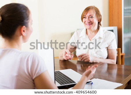 Smiling woman answer questions of social worker at home - stock photo