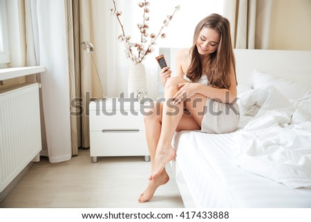 Smiling woman applying cream on legs on the bed at home - stock photo