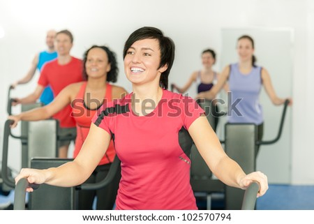Smiling woman at fitness class gym workout on treadmill - stock photo