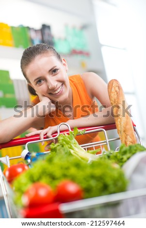 Smiling woman at supermarket with full shopping cart and shelves on background. - stock photo