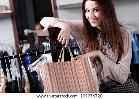 Smiling woman carries paper bags at the store - stock photo
