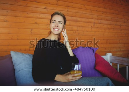 Smiling woman CEO having pleasant smart phone conversation, while is waiting business partners in modern coffee shop. Happy female is calling via cellphone during rest in hipster coffee shop interior