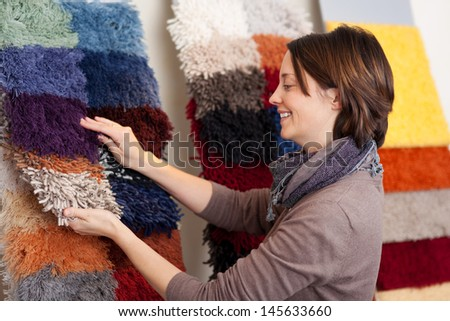 Smiling woman choosing carpet samples from a colorful display on the wall of a retail shop - stock photo