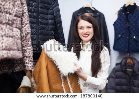 Smiling woman choosing jacket at clothing store - stock photo