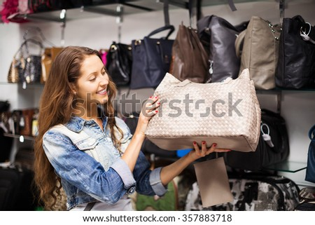 Smiling woman choosing leather bag in shop
